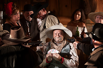 Poker players depicted playing in the Wild West
